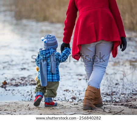 mother walking with small baby (baby first steps) - stock photo
