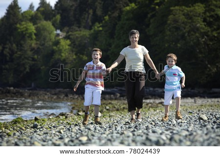 mother walking with two boys on a beach