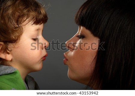 Mother was kissing her little son, son looking on lips