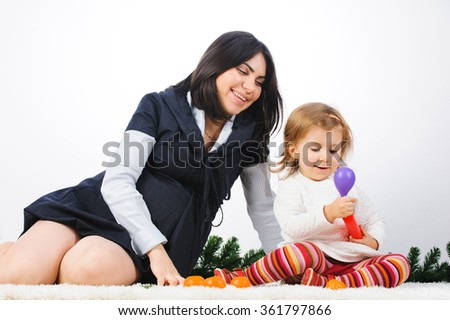 mother watching daughter blowing violet balloon - stock photo