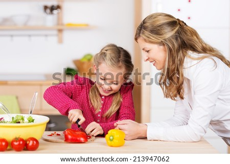 Mother watching her daughter prepare the meal as she leans on the counter with a happy smile while the little girl chops fresh vegetables - stock photo