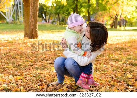 Mother with a baby hugging in the autumn park