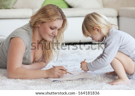 Mother with a child drawing together on a carpet at home - stock photo