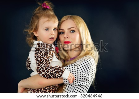 Mother with a child on a black background in the studio - stock photo