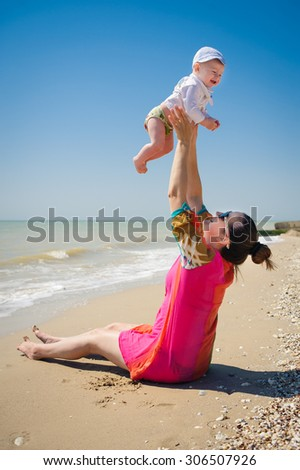 Mother with a child on the beach - stock photo