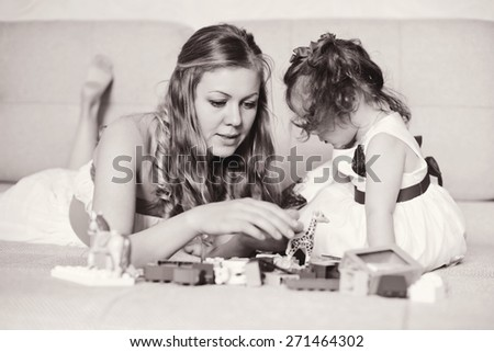 Mother with a little daughter playing with blocks at home - stock photo