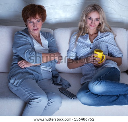 Mother with adult daughter watching television. Women looking film - stock photo