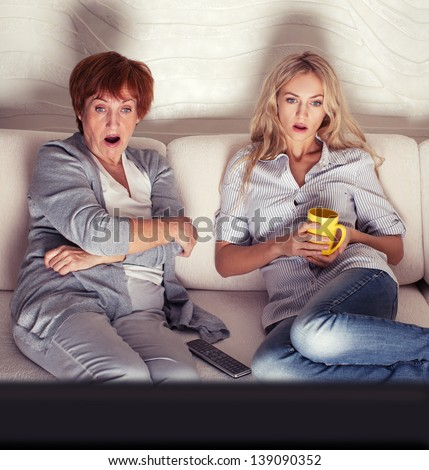 Mother with adult daughter watching television. Women looking film thriller - stock photo