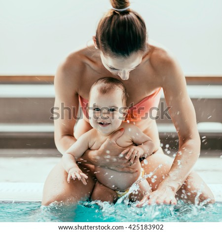 Mother with baby boy sitting on the swimming pool edge and splashing. - stock photo