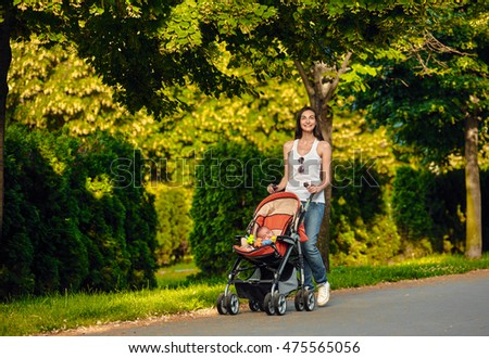 Mother with baby carriage outdoor summer
