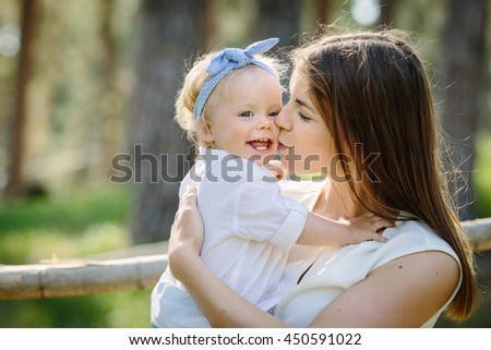Mother with baby her little daughter kiss and play outdoor in the park - stock photo