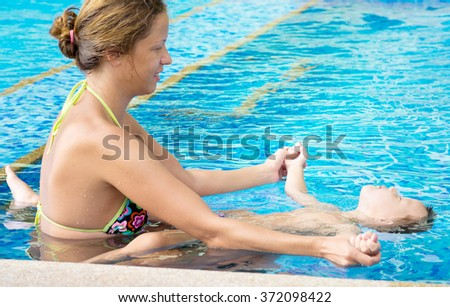 mother with baby in swimming pool