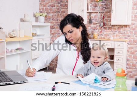 Mother with baby in the kitchen working with documents and speaks by phone - stock photo