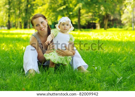 Mother with baby on the meadow - stock photo