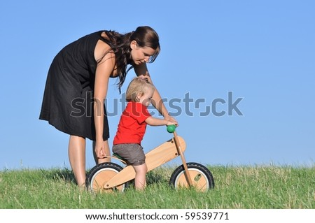 Mother with baby on the meadow with bike - stock photo