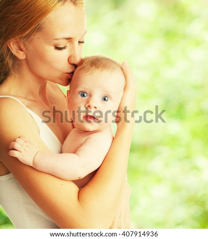 Mother with baby outdoors. Happy family with newborn in summer - stock photo