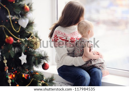 Mother with baby sitting by the window. Christmas decorations. On Christmas, waiting for a miracle. A woman with a child looking out the window.