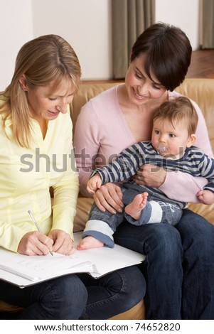 Mother With Baby Talking With Health Visitor At Home - stock photo