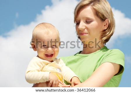 Mother with baby under blue clear sky - stock photo