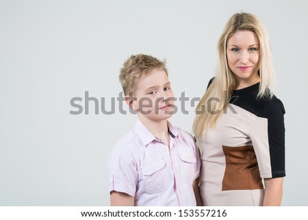 Mother with blond hair and a son with disheveled hair in the studio - stock photo