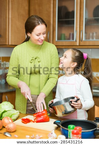 Mother with cheerful little daughter cooking together at home kitchen and smiling - stock photo
