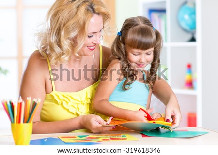 Mother with child girl drawing and cutting together - stock photo