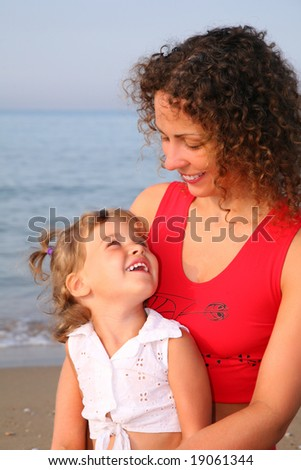 Mother with child on beach - stock photo