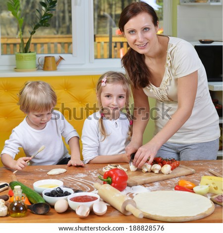 mother with children cut vegetables for pizzas