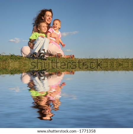 mother with children on grass and water - stock photo