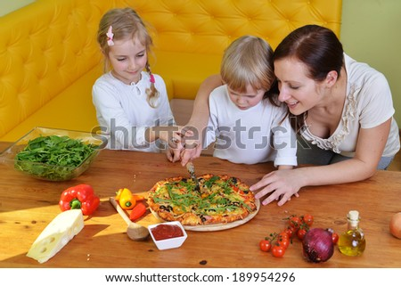 mother with children preparing to eat fresh pizza