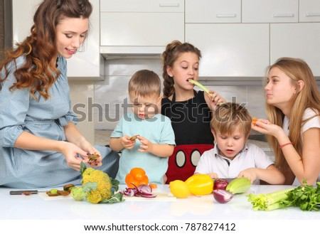 mother with children preparing vegetables in the kitchen