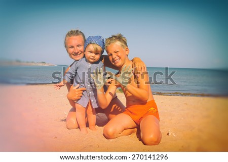 mother with children resting by the sea. summer . Photo instagram style. vintage retro. - stock photo