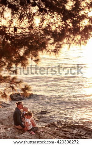 Mother with children sitting, cuddling on a rocky beach, watching the sunset and enjoying their bonding time together. Family values, tranquility and serenity concept.  - stock photo