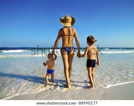 mother with children walk in a tropical beach - stock photo