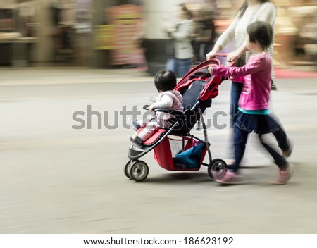 Mother with children walking in urban commercial street, blurred motion background