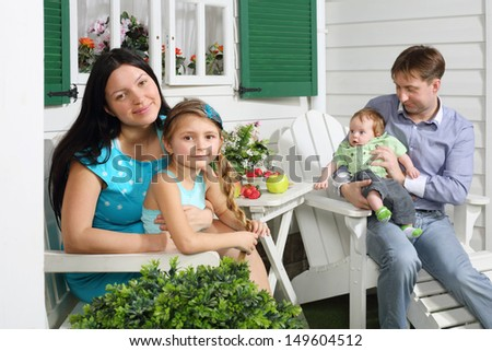 Mother with daughter and father with son sit at white table next to their house. Focus on woman and girl.