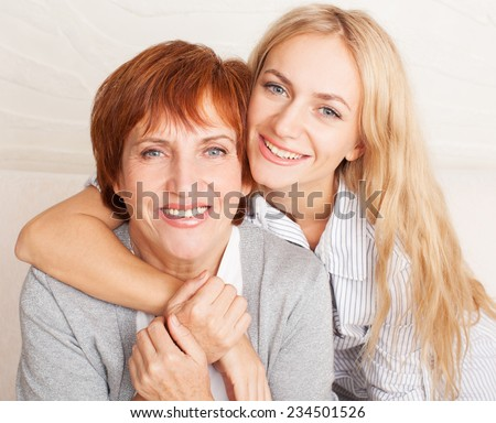 Mother with daughter at home. Happy women sitting at sofa. Family - stock photo