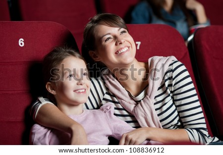 Mother with daughter enjoying time in the movie - stock photo