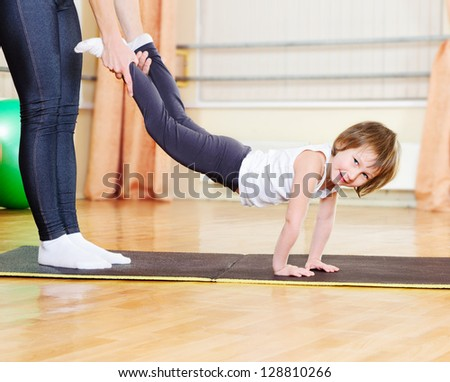 Mother with daughter exercising in sport hall - stock photo