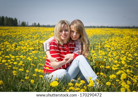mother with daughter in dandelion field - stock photo