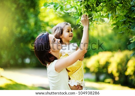 Mother with daughter in garden - stock photo