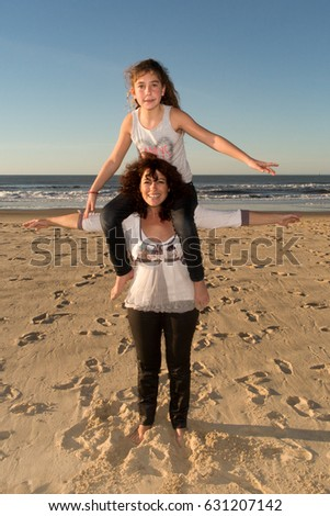mother with daughter making a piggyback on summer beach in holidays