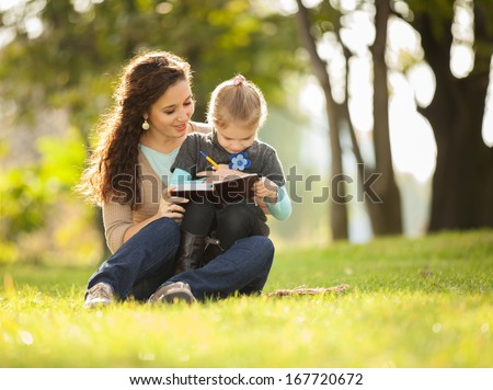 Mother with daughter playing in the park - stock photo