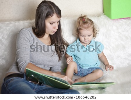 Mother with daughter read the book - stock photo