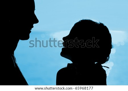 Mother with daughter sit ashore, opposite each other laugh - stock photo