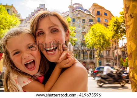 mother with daughter visiting barcelona rambla with gaudi house background - stock photo
