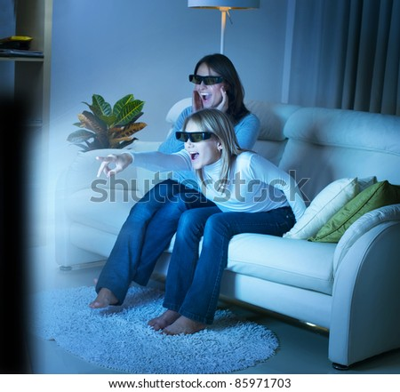 Mother with Daughter watching 3d film on TV - stock photo