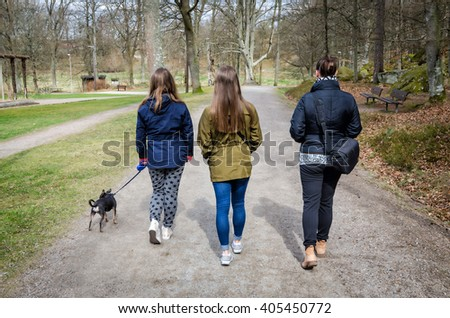 Mother with daughters and dog  walking in the spring park - stock photo