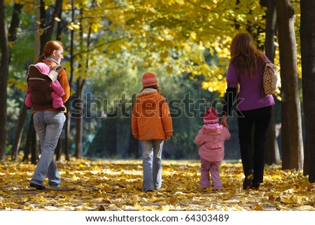 mother with daughters walking at the park - stock photo