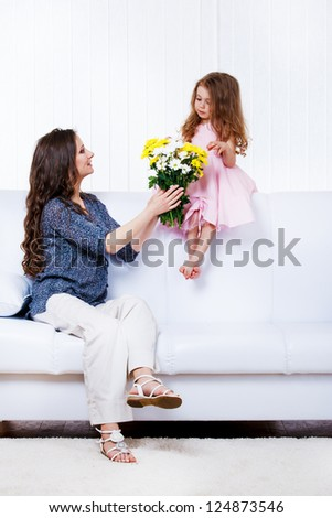 Mother with  flowers bouquet and little daughter sitting on sofa - stock photo